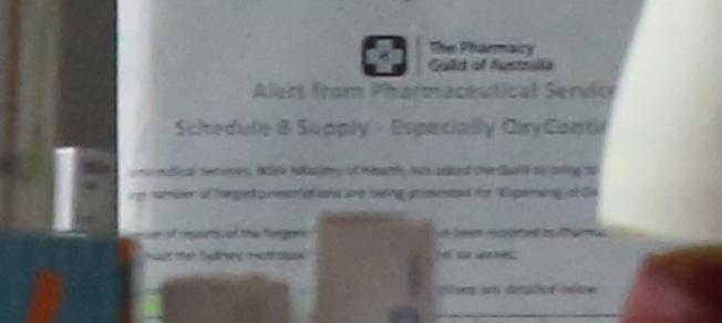 On the notice board behind where the pharmacists stand at Elias Pharmacy, we see this notice (blurred) from the Pharmacy Guild, referring to Schedule 8 (Drugs of Addiction). The notice is specifically about OxyContin.